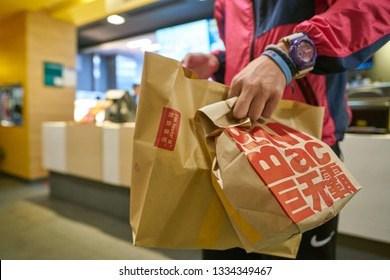 SHENZHEN, CHINA - CIRCA FEBRUARY, 2019: man hold brown paper bags with McDonald's food.