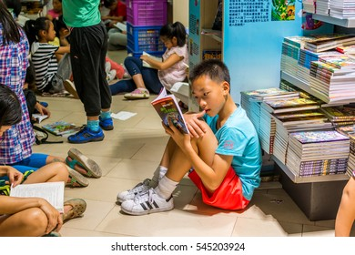 Shenzhen, China, December 21, 2016, Editorial: Chinese young school boys sitting on the floor and reading books at the Shenzhen Central Bookstore in Futian district, Shenzhen, China