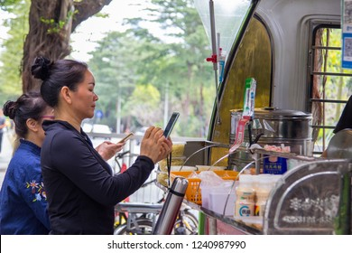 Shenzhen, China - November 14 2018: Two females pay their breakfast purchase at a street booth with Qr code payment. Cashless payment, in daily life is being widely accepted in China