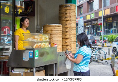 Shenzhen, China - November 14 2018: A female customer uses smartphone to pay her breakfast purchase at a street booth with Qr code payment. Cashless payment is widely accepted in China.