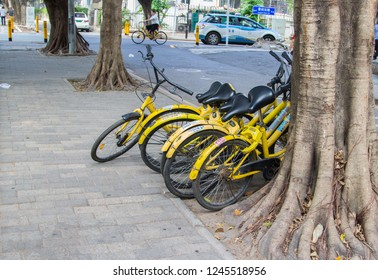 Shenzhen, China - November 14, 2018: Yellow bicycles of a bicycle sharing company carelessly parked in street. Too easy use of dockless system leads to disorder and clutter on sidewalk.
