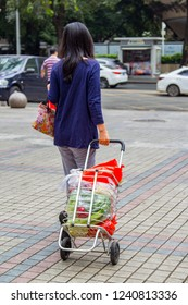 Shenzhen, China - November 24 2018: woman carrying groceries in shopping cart full of plastic shopping bags. Inconsiderate use of plastic bags is one of the biggest source of environment pollution.