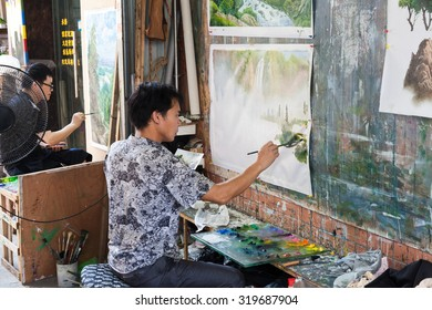 SHENZHEN, CHINA- SEPTEMBER 8: young artist of the Dafen Village at work in Shenzhen, Guangdong, China on September,8, 2015. They specialised in the making of replicas of oil paintings.