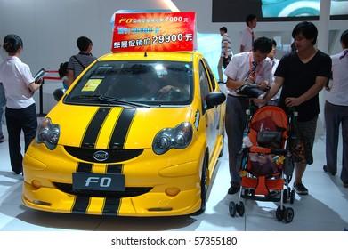 SHENZHEN - JUNE 14: Shenzhen-Hong Kong-Macao Auto Show, family watching BYD cars on June 14, 2010 in Shenzhen.