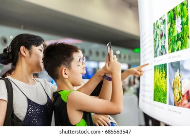 Shenzhen,China –July 25, 2017:Boy taking photo of the plant pictures with smart phone during the XIX International Botanical Congress in Shenzhen, Guangdong, China.