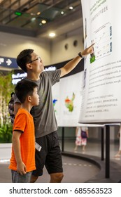 Shenzhen,China –July 25, 2017:Father and son visiting the exhibition during the XIX International Botanical Congress in Shenzhen, Guangdong, China.