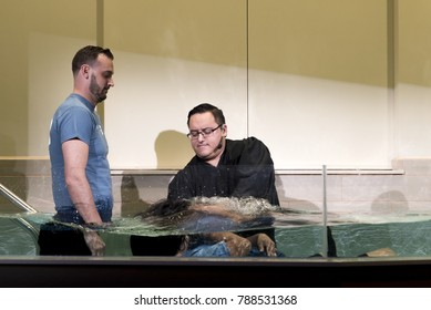 Shepherd Church, Los Angeles, California, USA, January 7, 2017: A pastor baptize a couple in church .Baptism is a Christian sacrament of admission and adoption, almost invariably with the use of water