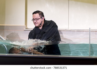 Shepherd Church, Los Angeles, California, USA, January 7, 2017: A pastor baptize a young boy. Baptism is a Christian sacrament of admission and adoption, almost invariably with the use of water.