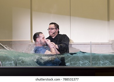 Shepherd Church, Los Angeles, California, USA, January 7, 2017: A pastor baptize a man. Baptism is a Christian sacrament of admission and adoption, almost invariably with the use of water.
