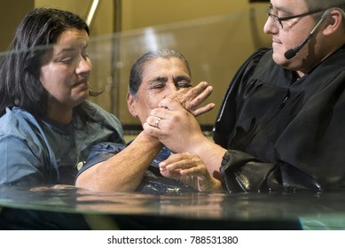 Shepherd Church, Los Angeles, California, USA, January 7, 2017: A pastor baptize a old woman. Baptism is a Christian sacrament of admission and adoption, almost invariably with the use of water.