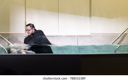Shepherd Church, Los Angeles, California, USA, January 7, 2017: A pastor baptize a boy in church .Baptism is a Christian sacrament of admission and adoption, almost invariably with the use of water.