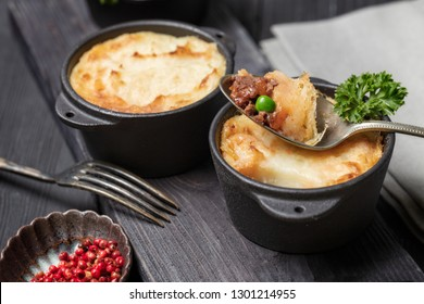 Shepherd's pie, british casserole in cast iron pan, with minced meat, mashed potatoes and vegetables, on dark background