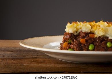 Shepherds pie shot front on on wood with grey background cropped close-up with negative space