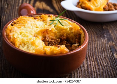 Shepherd's pie, traditional British dish with  minced meat and mashed potato on rustic wooden table