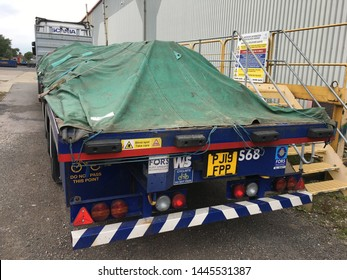 Sherburn, Yorkshire/ UK - June 18 2019: Scania Semi Truck with a Flatbed Trailer loaded with Sand Blasted Steel and covered with a Green Tarp and straps to protect the load from the Weather.