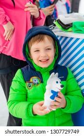 Sheregesh, Kemerovo Region - April 6, 2018. Boy holding U-Laika symbol of Universiade 2019 souvenir toy. Promo zone of the Universiade 2019 in Krasnoyarsk.
