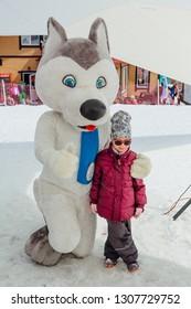 Sheregesh, Kemerovo Region - April 6, 2018. U-Laika symbol of Universiade 2019 hugging a little girl. Promo zone of the Universiade 2019 in Krasnoyarsk.