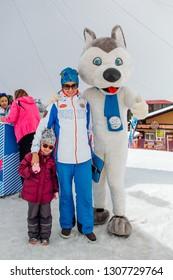 Sheregesh, Kemerovo Region - April 6, 2018. U-Laika symbol of Universiade 2019 hugging a little girl and her mother. Promo zone of the Universiade 2019 in Krasnoyarsk.