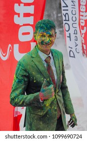 Sheregesh, Kemerovo region, Russia - April 14, 2018: Grelka Fest is a sports and entertainment activity for ski and snowboard riders in bikini. Man in business suit paunted with holi colors.