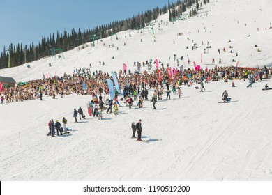 Sheregesh, Kemerovo region, Russia - April 16, 2016: Grelka Fest is a sports and entertainment activity for ski and snowboard riders in bikini. Crowd of people with snowboard and mountain ski on slope