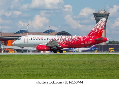 Sheremetyevo International Airport, Moscow, Russia - 06.14.2021. Passenger aircraft Sukhoi Superjet 100 (SSJ100) of Rossiya Airlines takes off from the airport runway. ATC Tower in the background.