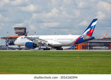 Sheremetyevo International Airport, Moscow, Russia - 06.14.2021. Passenger aircraft Airbus A350 XWB of Aeroflot - Russian Airlines taxiing on the airport runway. Airport terminal in the background.