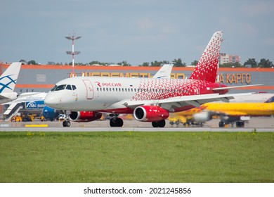 Sheremetyevo International Airport, Moscow, Russia - 06.14.2021. Passenger aircraft Sukhoi Superjet 100 (SSJ100) of Rossiya Airlines taxiing on the airport runway. Airport terminal in the background.