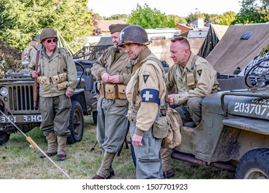 Sheringham, Norfolk, UK – September 14 2019. Group of men dressed up as 1940s US soldiers in vintage uniforms next to US military vehicles at the annual forties weekend in Holt Norfolk