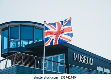 Sheringham, UK - April 21, 2019: Close of of a Union Jack flag in front of the Mo Museum in Sheringham, an English seaside town within the county of Norfolk, UK.