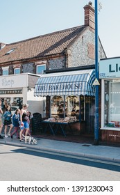 Sheringham, UK - April 21, 2019: People walking past The Bakehouse Bakery in Sheringham, an English seaside town within the county of Norfolk, UK.