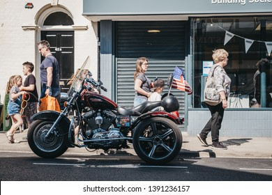 Sheringham, UK - April 21, 2019: People walking past Harley Davidson motorcycle parked on a side of the road in Sheringham, an English seaside town within the county of Norfolk, UK.
