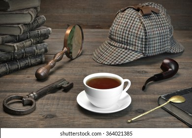 Sherlock Concept. Private Detective Tools On The Wood Table Background. Deerstalker Cap,  Magnifier, Key, Cup, Notebook, Smoking Pipe.Overhead View