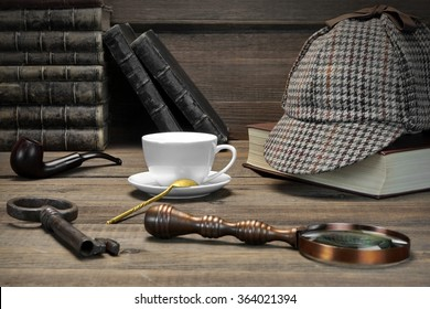 Sherlock Concept. Private Detective Tools On The Wood Table Background. Deerstalker Cap,  Magnifier, Key, Cup, Notebook, Smoking Pipe. Front View