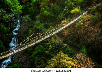 Sherpa with baggage crossing sunlit suspension bridge in Nepal, Langtang valley
