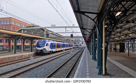 's-Hertogenbosch / Netherlands - April 12 2018: A modern dutch NS sprinter train on the station of Den Bosch / 's-Hertogenbosch with old 19th century roofs. The train is a Stadler Flirt 3.