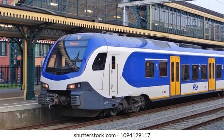 's-Hertogenbosch / Netherlands - April 12 2018: The front of a modern dutch NS sprinter train on the station of Den Bosch / 's-Hertogenbosch with old 19th century roofs. The train is a Stadler Flirt.