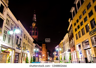 's-Hertogenbosch, Netherlands - december 15 2015: Kerkstraat in Den Bosch at night with a view on it's shopping windows and colorful facades and the Sint-Jan Cathedral.
