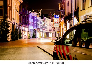 's-Hertogenbosch, Netherlands - December 15 2015: Kerkstraat in Den Bosch at night with a view on it's shopping windows and colorful facades and a police car.