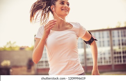 She's happy when she's exercising. Young happy woman running. Close up..