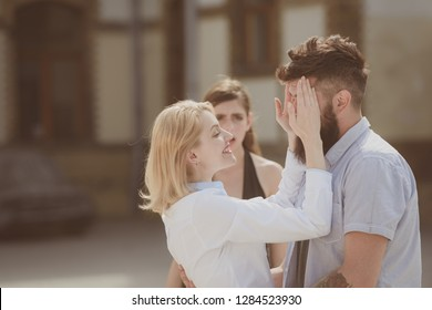 Shes jealous of their relationship. Jealous woman look at couple in love on street. Romantic couple of man and woman dating. Bearded man cheating his woman with another girl. Unhappy jealous girl.
