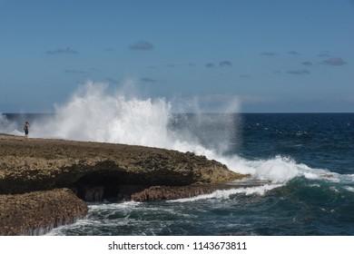 Shete Boka, Curacao - March 02, 2018: Tourist taking photo of big splash at Shete Boka national park, Curacao