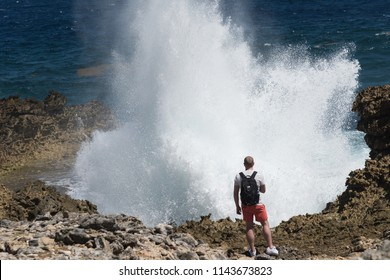 Shete Boka, Curacao - March 02, 2018: Tourist taking photo of big splash at Boka Pistol in Shete Boka national park, Curacao