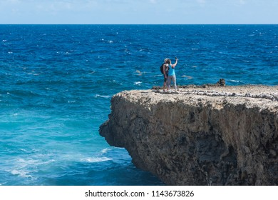 Shete Boka, Curacao - March 02, 2018: Couple taking selfy with phone on the cliff at Shete Boka national park, Curacao