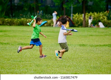 Sheung Wan, Hong Kong - 26 August 2018: Kids playing plane toy with friend at the park.
