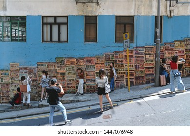 SHEUNG WAN, HONG KONG - MARCH 31, 2018 : Tourists taking pictures with graffiti on wall. It is a common find in Hong Kong and Sheung Wan is a highly popular place for graffiti and street art.