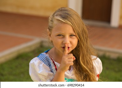 Shh, hush, my mom is sleeping. Frustrated little girl shows silence gesture with hand finger to her mouth isolated outside external house wall on background