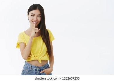 Shh keep it between us. Charming mysterious and flirty young woman in trendy yellow t-shirt making shush gesture with index finger over mouth smiling and posing over grey wall, keeping secret