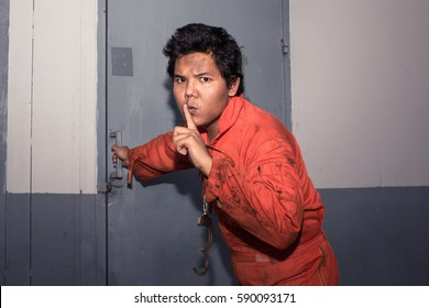 Shh!! orange jumpsuit prisoner make silence gesture while break the jail