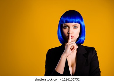 Shh! Portrait with copy space empty place for advertisement of mysterious charming girl in vivid blue wig gesturing silence sign with forefinger isolated on yellow background