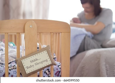 Shhh baby sleeping sign on cot with mother holding and feeding baby on bed in room